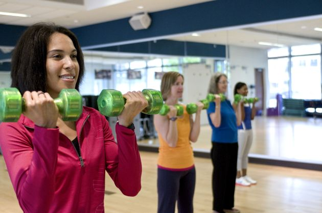 Happy girl using light weight dumbbells on fitness