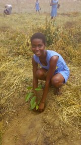 HAPPY STUDENT WITH HER PLANTED TREE