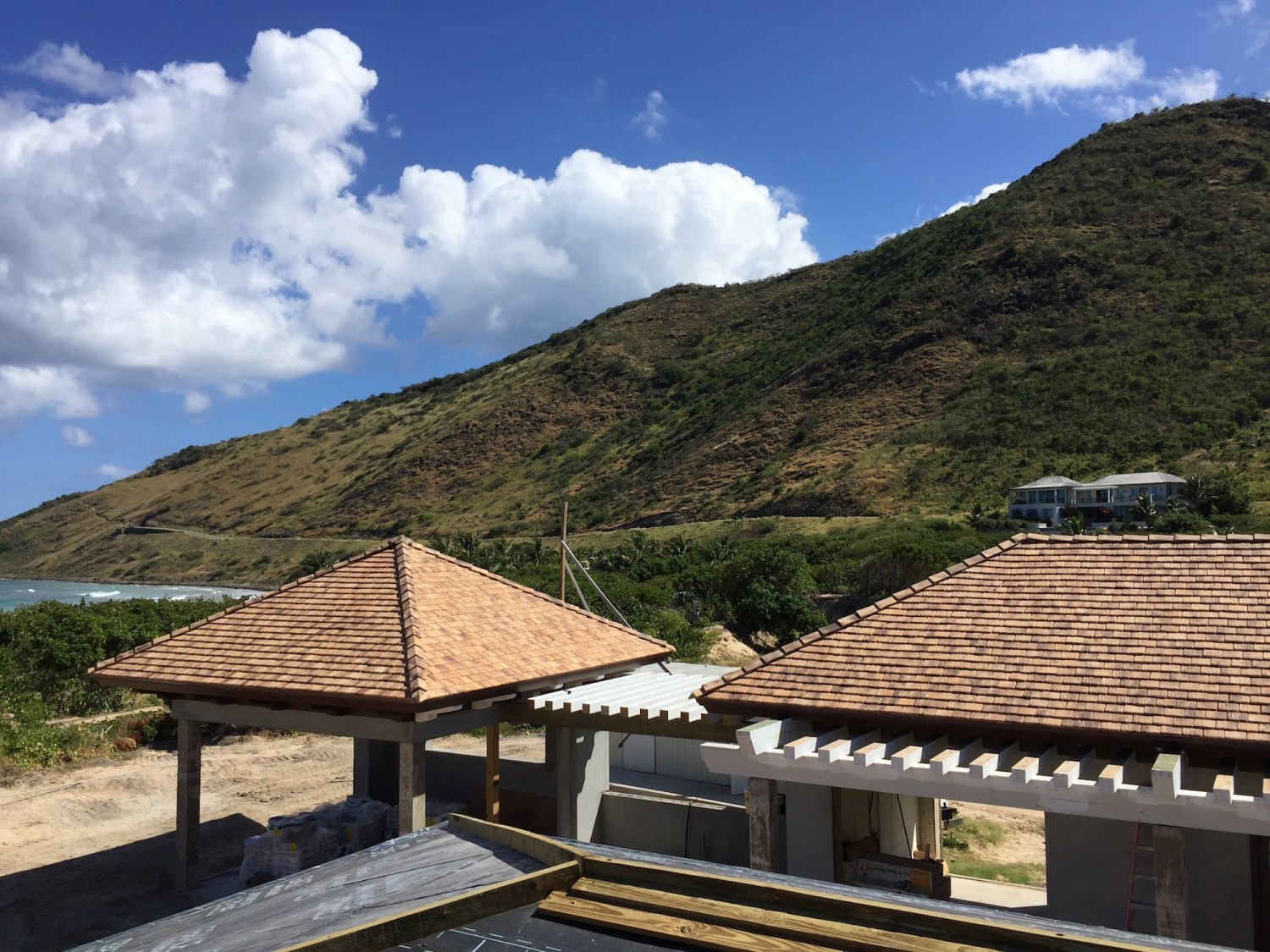 Rugged St. Kitts mountains as seen from the clay-tiled roofs of an MMA project.