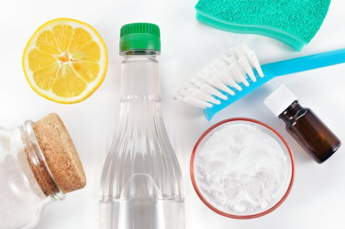 Eco-friendly natural cleaners. Vinegar, baking soda, salt, lemon and essential oil. Homemade green cleaning on white background.