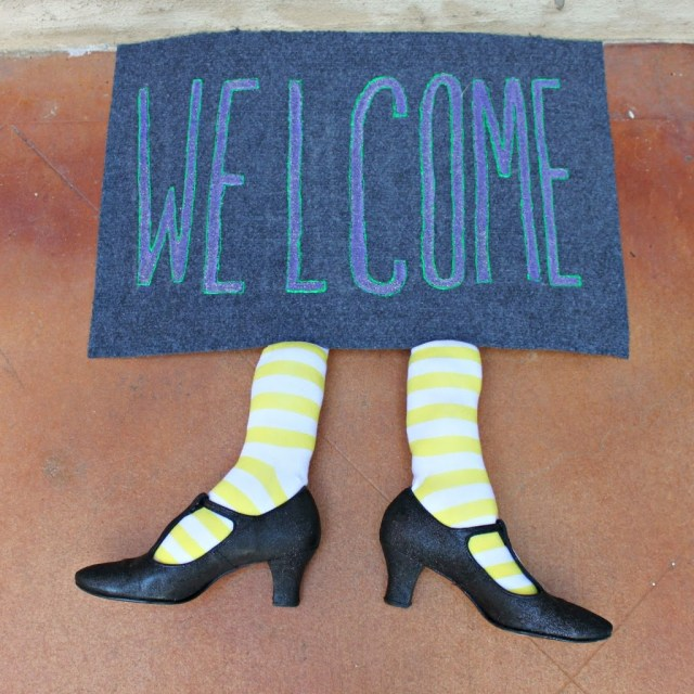 Make a witch welcome mat to decorate your porch with for Halloween! Use thrift store and dollar store items to make this hilarious decor.