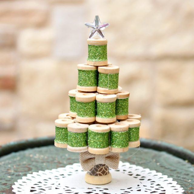 Turn tiny wooden spools into an adorable miniature Christmas tree ornament! Fun project to make and to display. I
