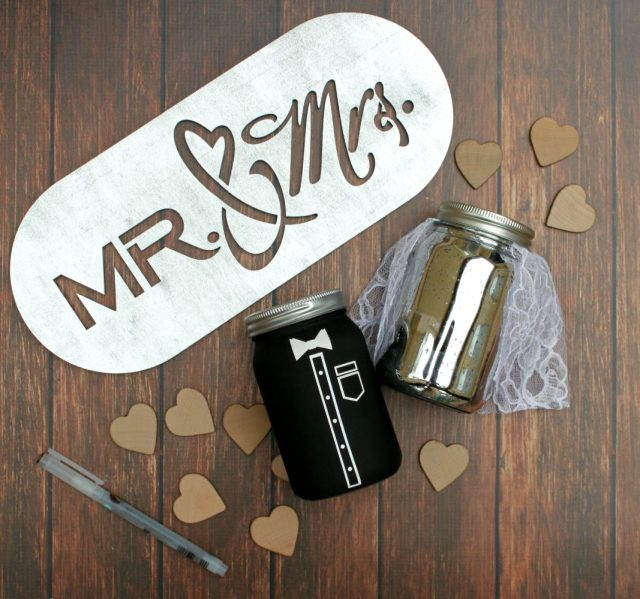 Make a unique guestbook by creating a mason jar bride and groom. Guests will sign and drop wood hearts into the jars! Free file with tutorial.