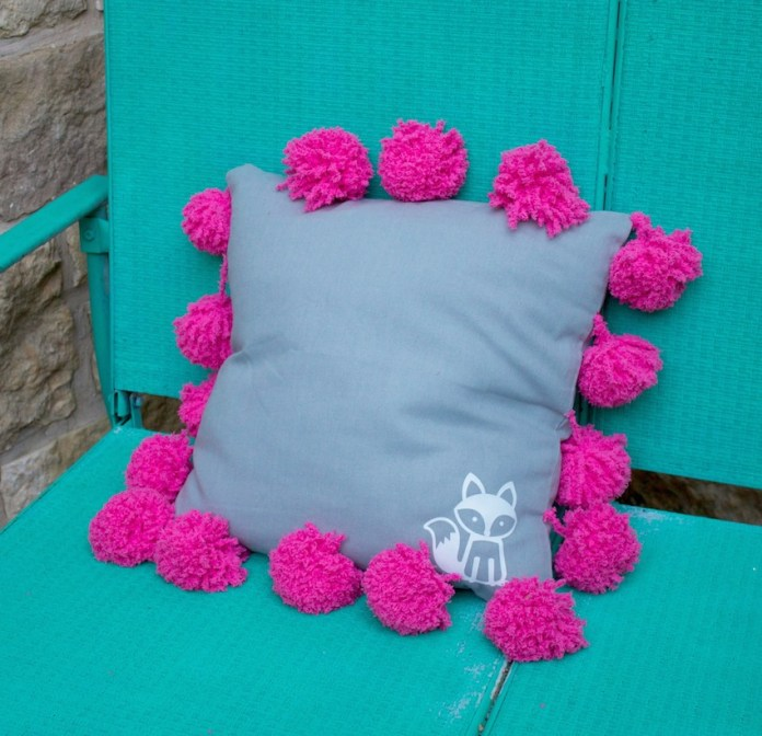This pom pom pillow tutorial is an adorable and easy to make piece of home decor. This fluffy and fuzzy accent pillow makes a great gift, too.