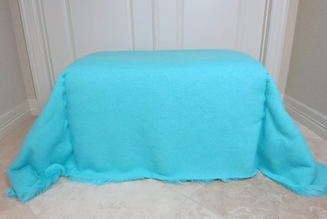 "For example, if you measure 48"" from the front to the back of the ottoman and 36"" from one side to the other side, then you will cut a rectangle of fur fabric that is 48x36 inches. I used approximately 2 yards of fabric for my ottoman makeover."