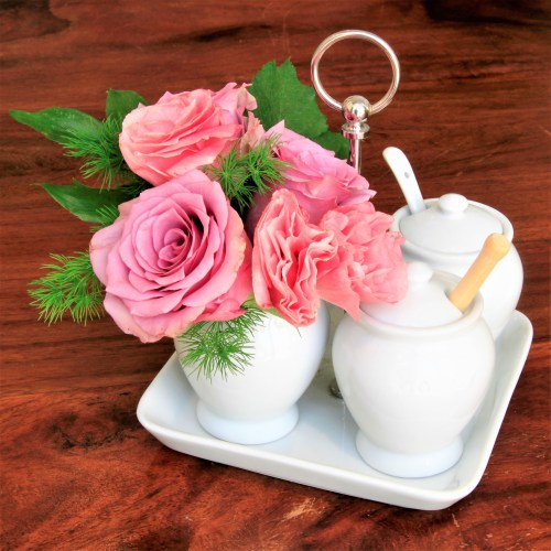 A posy of pink flowers in a small white china jug, placed on a white china tray with sugar bowl and cream jug