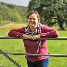 Porttait photo of Mel, standing at a gate in a Scottish field