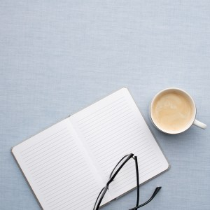 Open notebook next to a cup of coffee and reading glasses ready to get organised