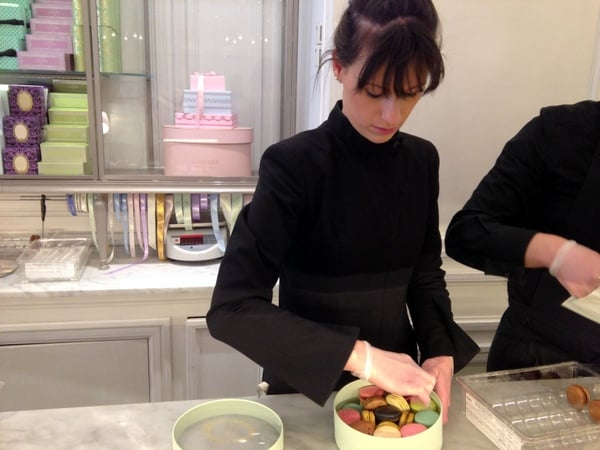 Gloved-saleslady carefully packing a box of macarons