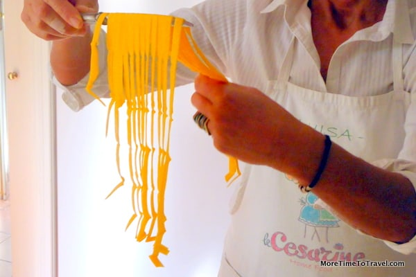 Luisa holds up the tagliatellle on a knife to create a nest