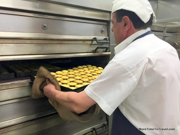 Baker placing a tray of tarts in the 900-degree oven
