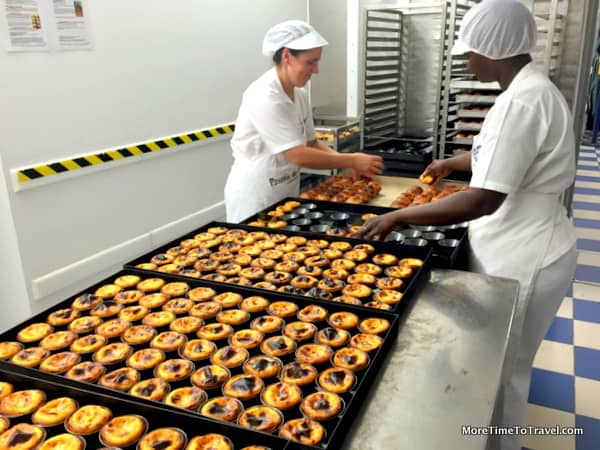 Women taking warm tarts out of the baking trays