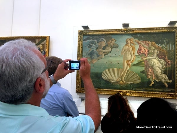 Tourists stop to take photographs of the masterpieces in the Uffizi
