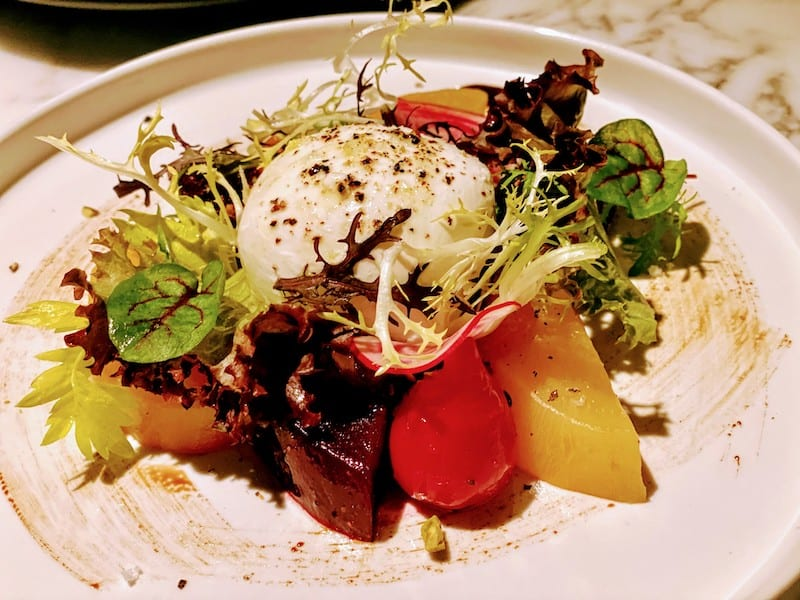 Burrata appetizer with fresh roasted beets, poached fruit and Sicilian pistachios