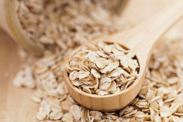 a wooden spoon holding uncooked oats to measure out oat flour