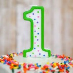 a green and white number 1 candles on top of a healthy smash cake with rainbow sprinkles