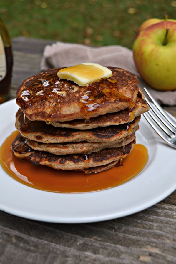 Stack of apple cinnamon pancakes on a white plate with a silver fork on a wooden picnic table. A pat of butter is melting on top and syrup is dripping down the sides with an apple on a brown dish towel in the background