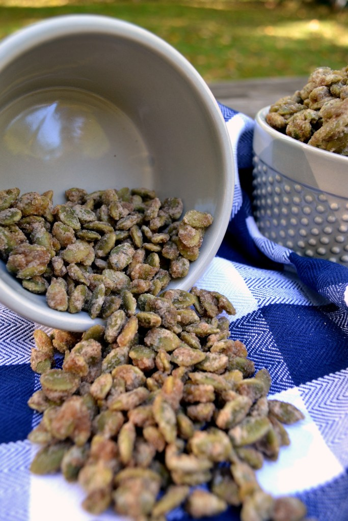 a grey bowl spilling out candied pumpkin seeds onto a blue gingham dish towel