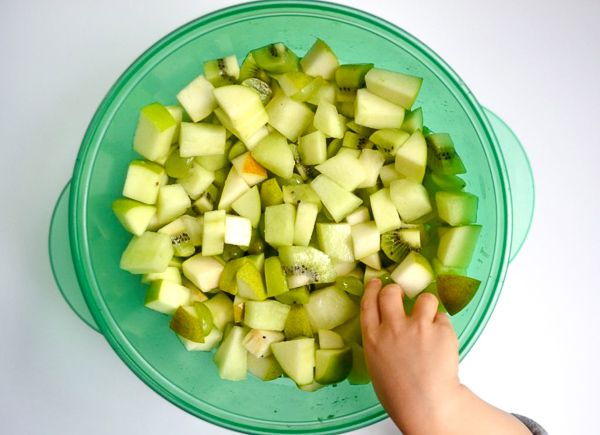 A little hand dips into a large green bowl to take a taste of this green fruit salad