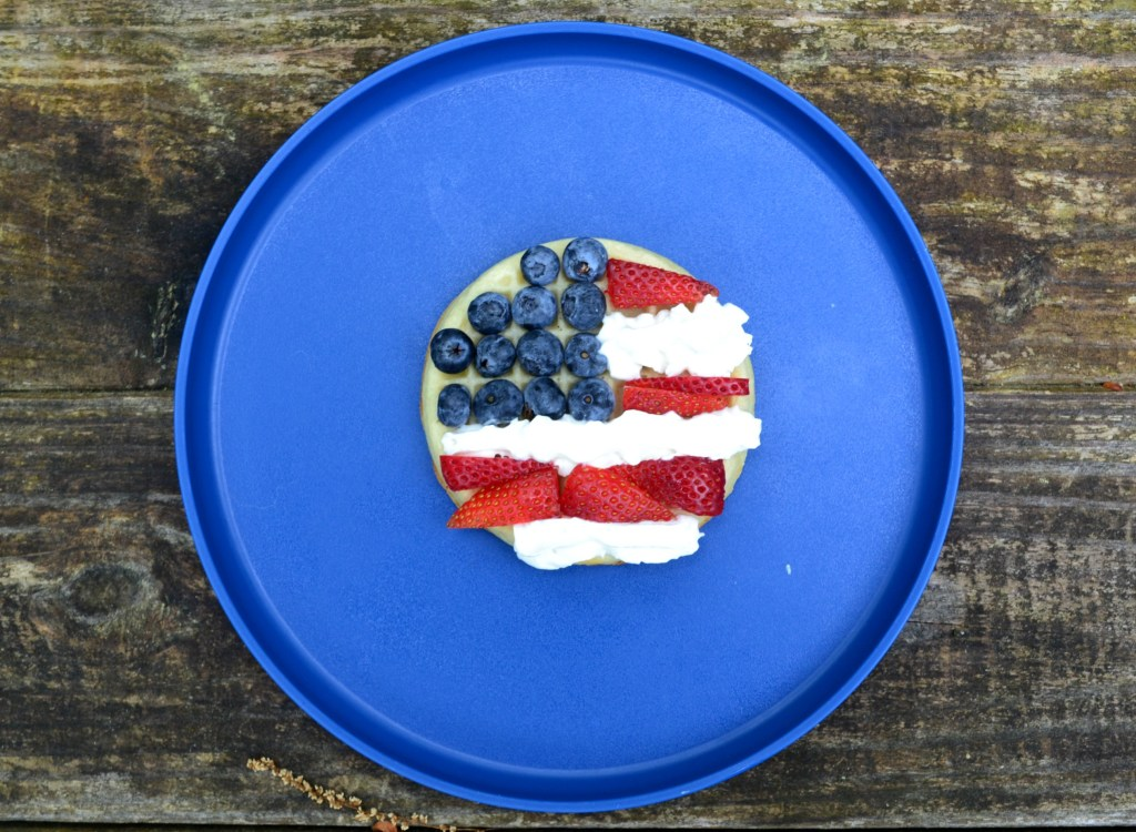 an american flag on a waffle using whipped cream, strawberries, and blueberries, on a blue plate and a wooden table.