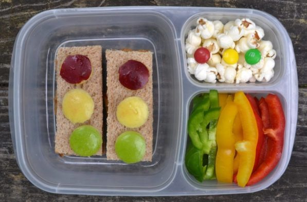 a stop light lunch box with traffic light sandwiches, popcorn and bell peppers.