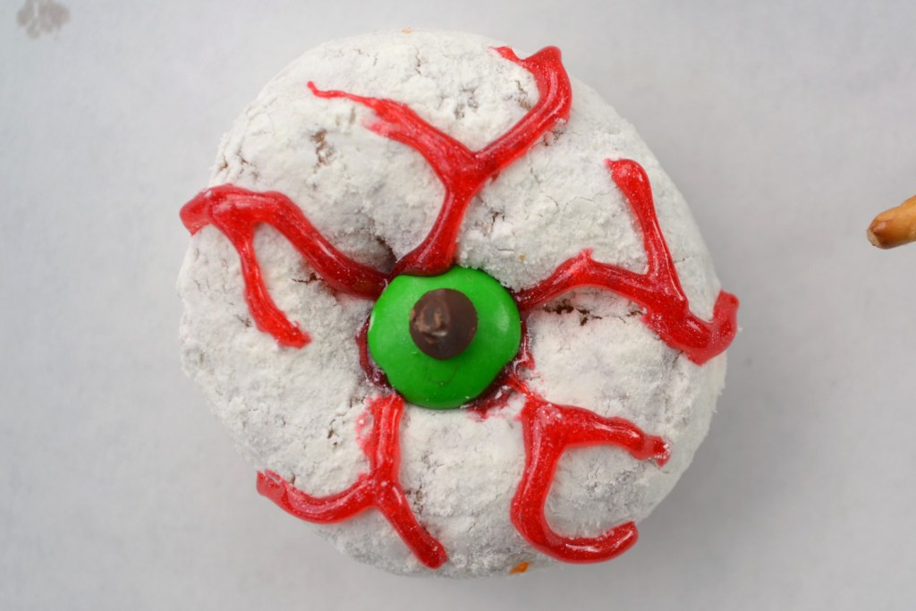 a spooky eyeball donut made with red decorating frosting to make veins and a green mm for the iris