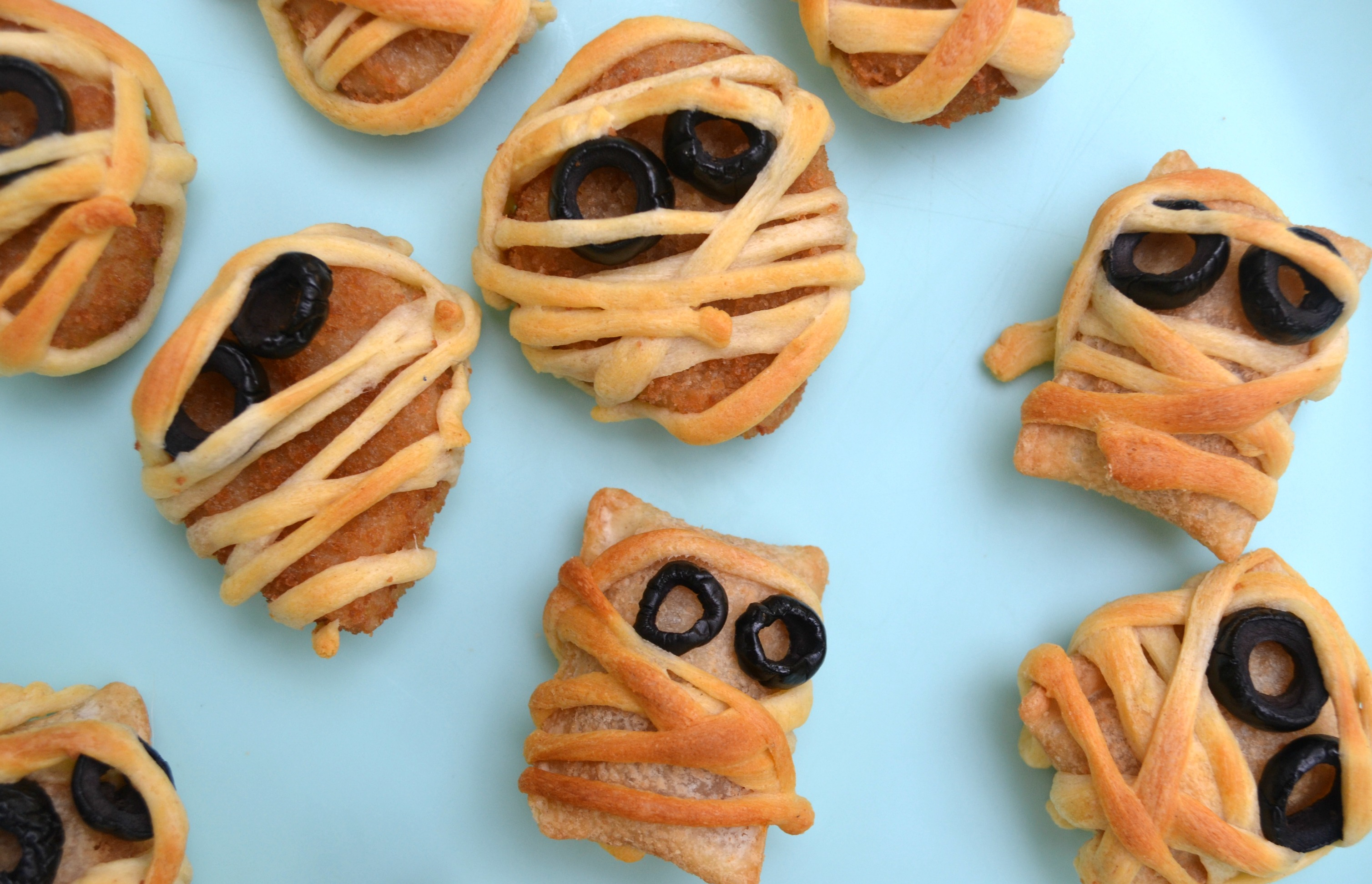 halloween mummy snacks on a blue background - chicken nuggets and pizza rolls rolled in thin strips of crescent roll with olive eyes.