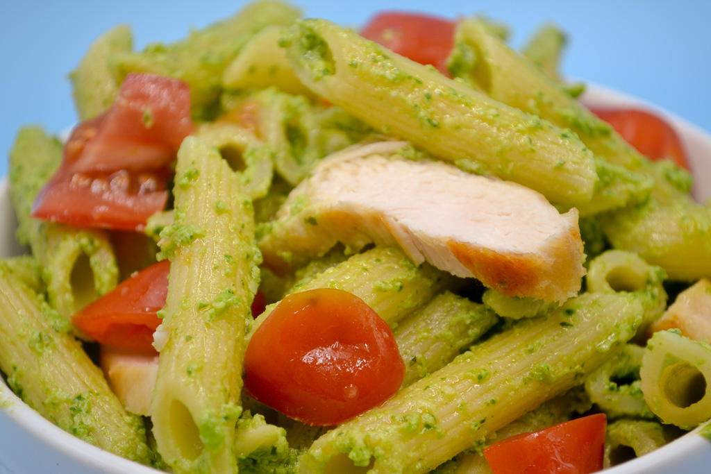 a close up of Vegetable Pesto Pasta Sauce. Penne noodles covered in sauce with grilled chicken and red grape tomatoes.