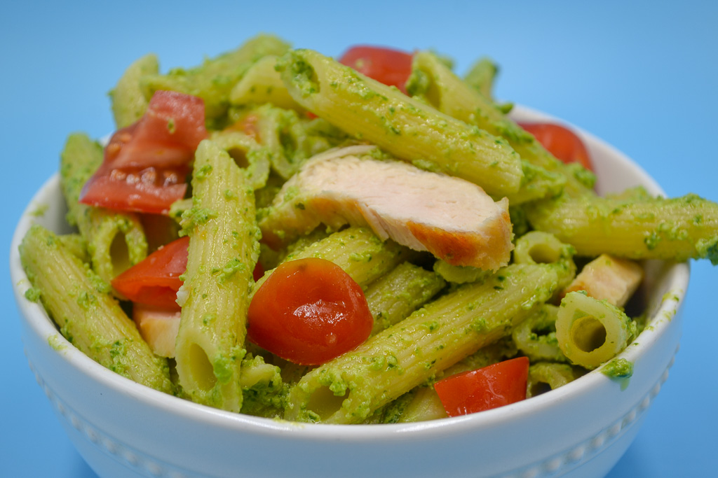 a white bowl with penne pasta covered in vegetable pesto pasta sauce with grape tomatoes and grilled chicken