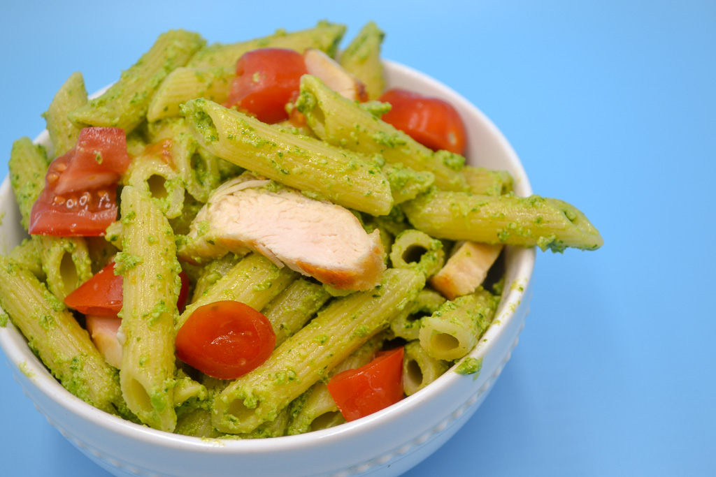 a white bowl stuffed with penne pasta covered in vegetable pesto pasta with chicken and tomato on a blue background.