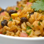 a closeup of mexican fried rice in a white bowl on a grey background with cilantro