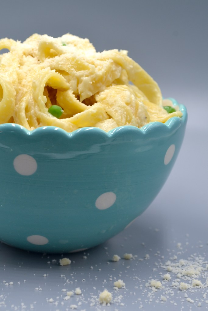 a bowl of fettuccine and peas covered in healthy alfredo and topped with parmesan cheese in a blue bowl with white polka dots on a grey background with parmesan cheese on the base.