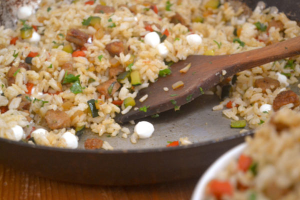 A flat wooden spoon stirring an italian fried rice recipe in a large pan