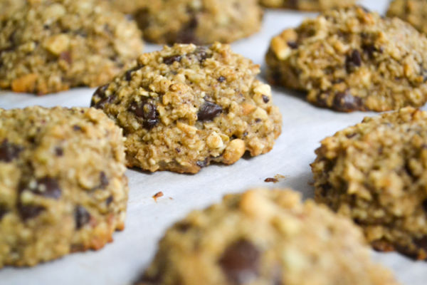 healthy banana cookies lined up on a cookie sheet lined with white parchment paper.