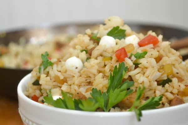 italian fried rice in a white bowl with fresh parsley and mini mozzarella balls