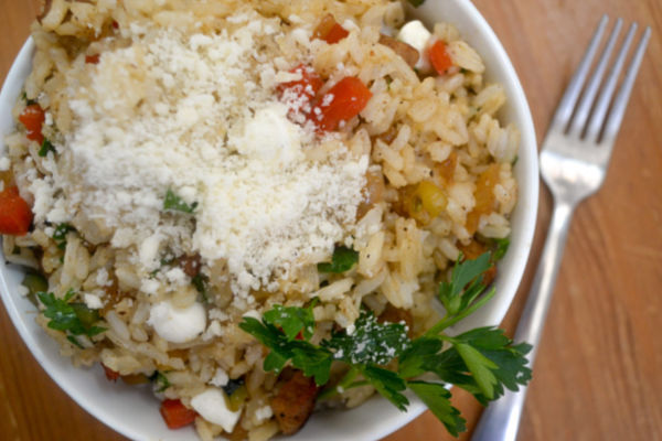 a bowl filled with Italian Fried Rice recipe topped with parmesan cheese in a white bowl