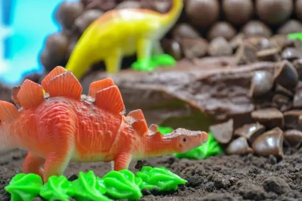 a red toy stegosaurus with green frosting at the bottom on a dinosaur birthday cake