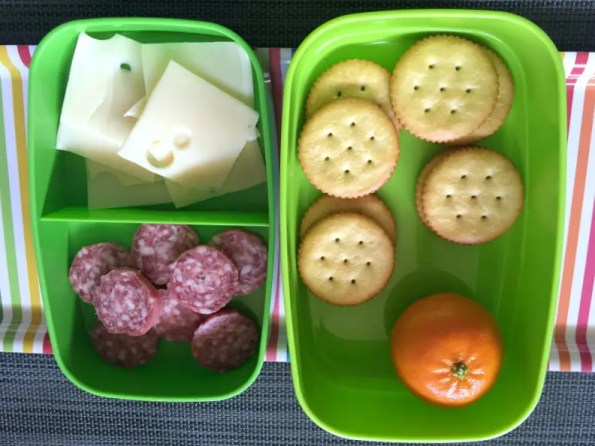 A photo o a DIY lunchable with salami, swiss, crachers, and a clementine in a green sectioned container