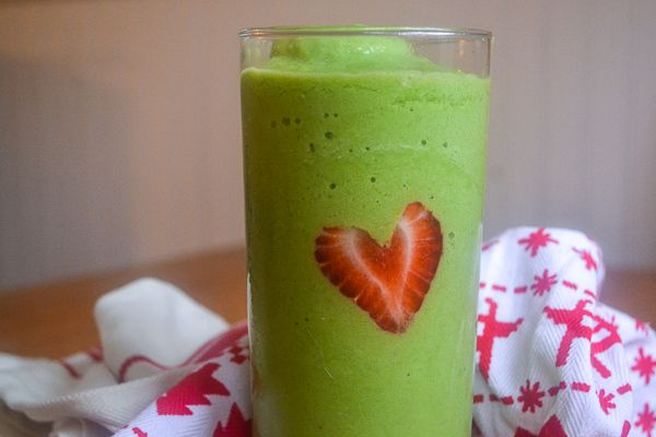 A closeup of a green smoothie with a strawberry cut into a heart to make a grinch christmas smoothie with a red and white christmas dish towel
