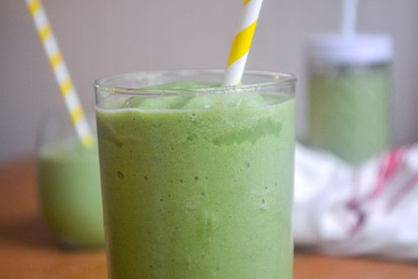 a close up of the top of a narrow glass filled with green spinach smoothie with a yellow and white striped straw