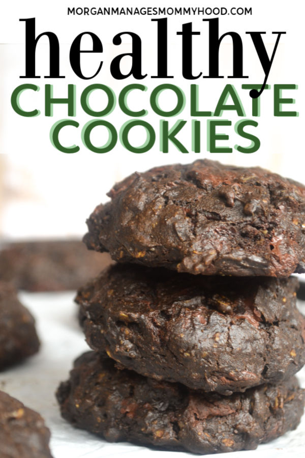 three chocolate spinach cookies stacked on a marble countertop