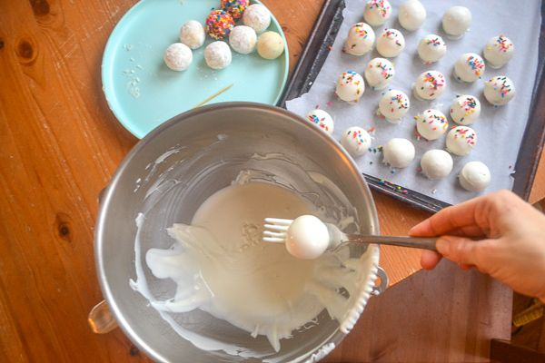 a large silver mixing bowl with white chocolate and a hand holding a fork that is being used to dip a no bake cheesecake bite into it. On a wood table there is a sheet tray with finished cheesecake bites.