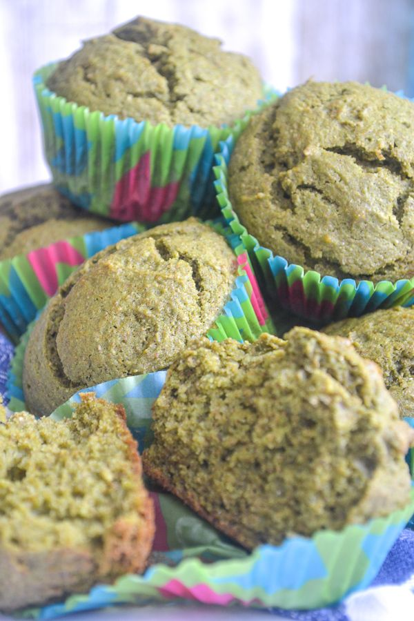 a large stack of green muffins on in bright muffin liners with one muffin opened in half in the front to show the soft middle.