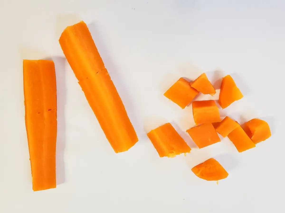 steamed carrot sticks and steamed carrot diced on a white background for baby led weaning