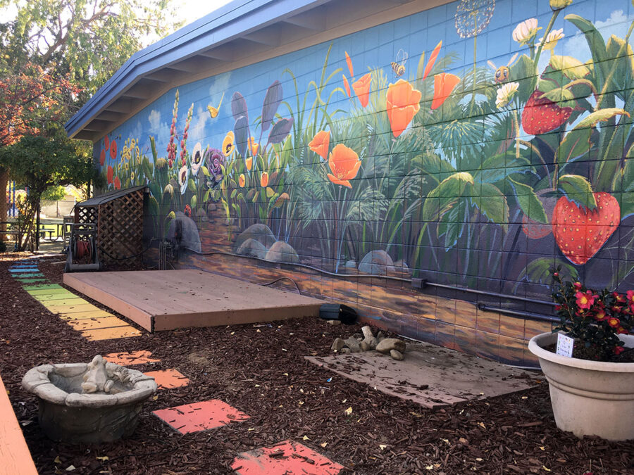 Flower mural of California Poppies, Strawberries, Foxgloves, and Pansies at a School