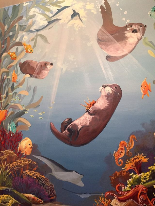 Sea otter mural with clownfish, dolphins, seahorses, and stingrays
