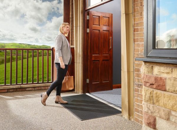 Woman walking into a building across a Morland Access Approach Industrial Rubber doormat, with greem hills in the background