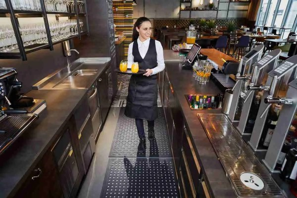 Bar server behind a bar carrying a tray with two glasses of orange standing on a Morland Service Anti bacterial rubber industrial doormat