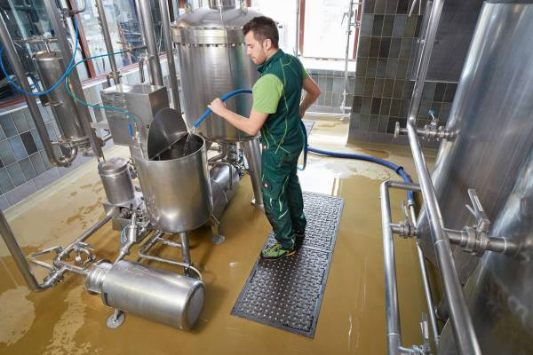 A man in a green overalls using a blue hose to fill a stainless steel tank with water white standing on a Morland Service Anti Bacterial Industrial rubber Doormat