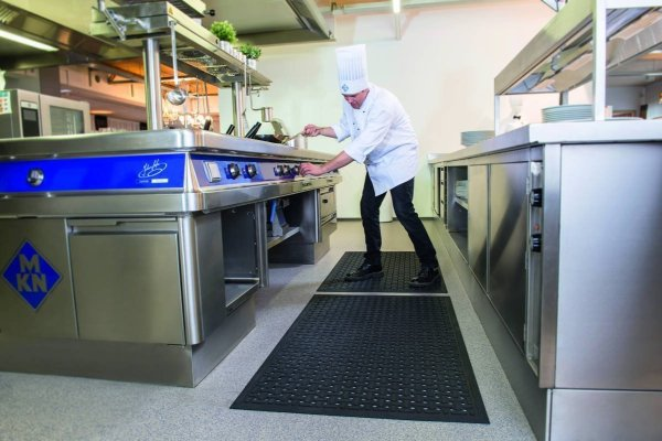 A Chief at a stove in a commercial kitchen with large frying pan stood on a Morland Service Anti bacterial rubber industrial doormat